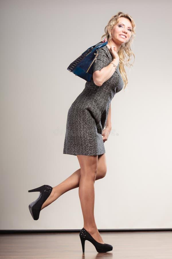 La femme d'affaires mûres tient le sac à main photos stock