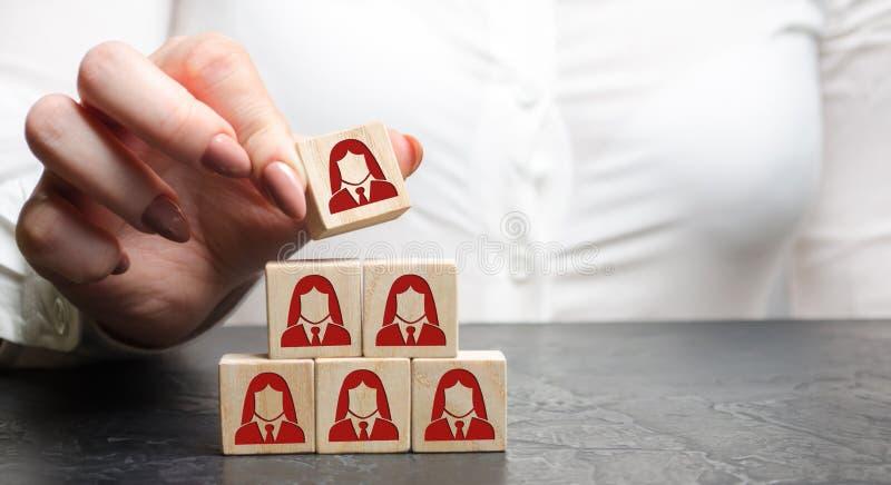 La femme d'affaires met les blocs en bois avec l'image des employés féminins Le concept de la gestion dans une équipe Ressources  photos stock
