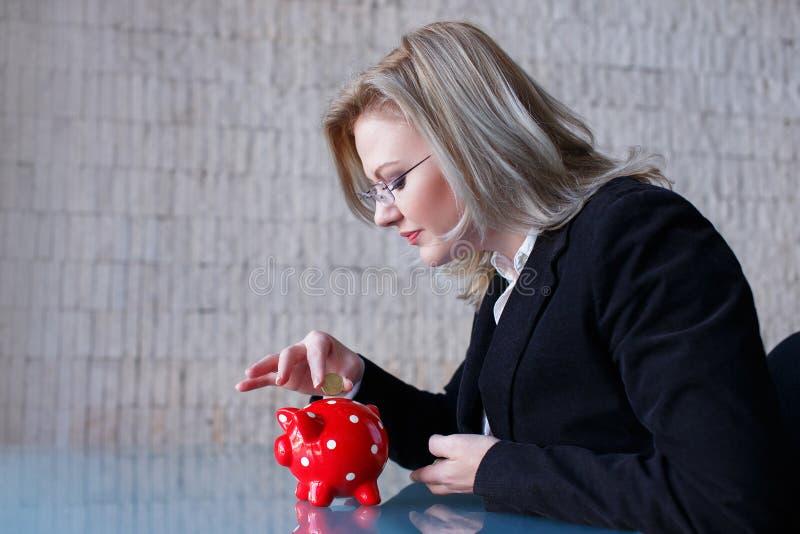 La femme d'affaires a mis des pièces de monnaie dans la tirelire images stock
