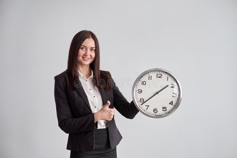 La femme d'affaires montre sur la grande horloge ronde, sur un fond gris de mur dans le bureau images libres de droits
