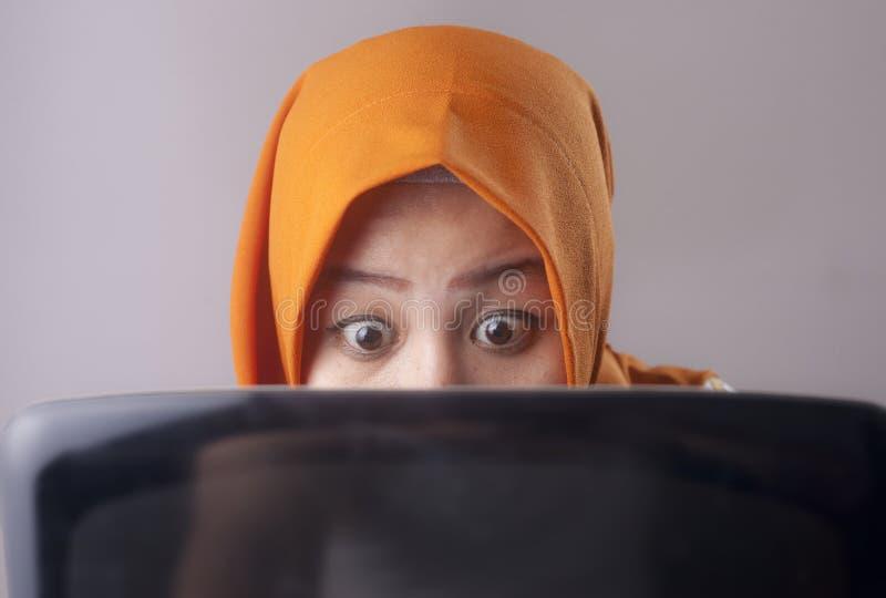 La femme d'affaires musulmane Working sur l'ordinateur portable a choqu? le geste stunned photo stock