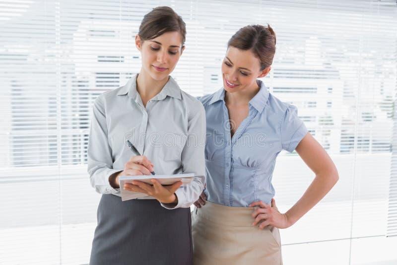 La femme d'affaires observant son collègue écrivent sur le presse-papiers photos stock
