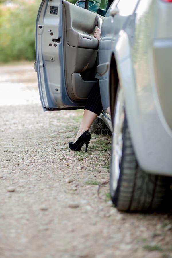 La femme d'affaires posant pr?s de la voiture blanche et montrant les jambes minces et minces elle s'approchent de sa voiture Dam photographie stock