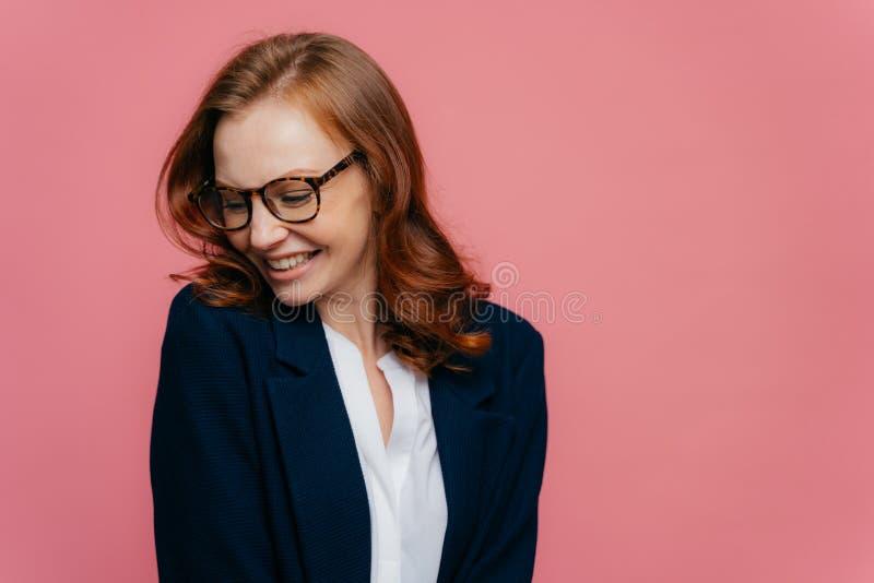 La femme d'affaires positive élégante focalisée de côté, a le sourire sincère, porte des lunettes, habillés dans le costume forme photos stock