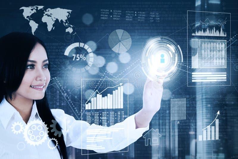 La femme d'affaires réussie appuie sur un bouton virtuel photos stock