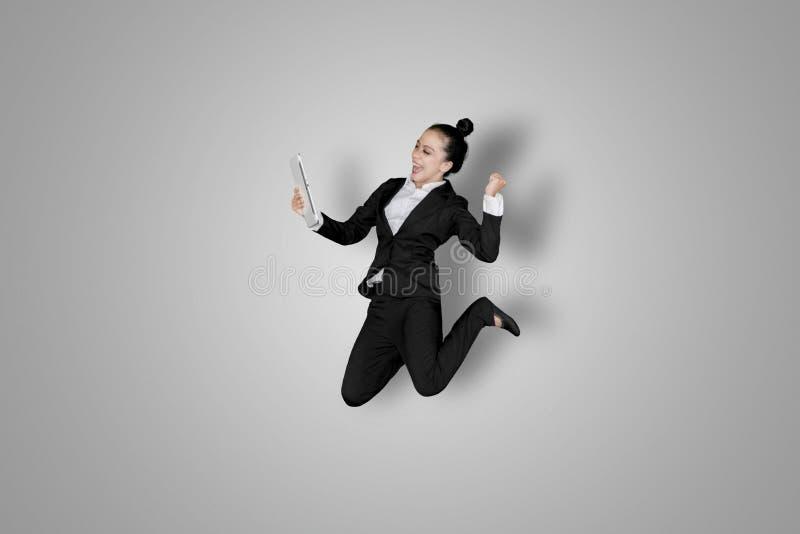 La femme d'affaires réussie saute avec le comprimé image libre de droits