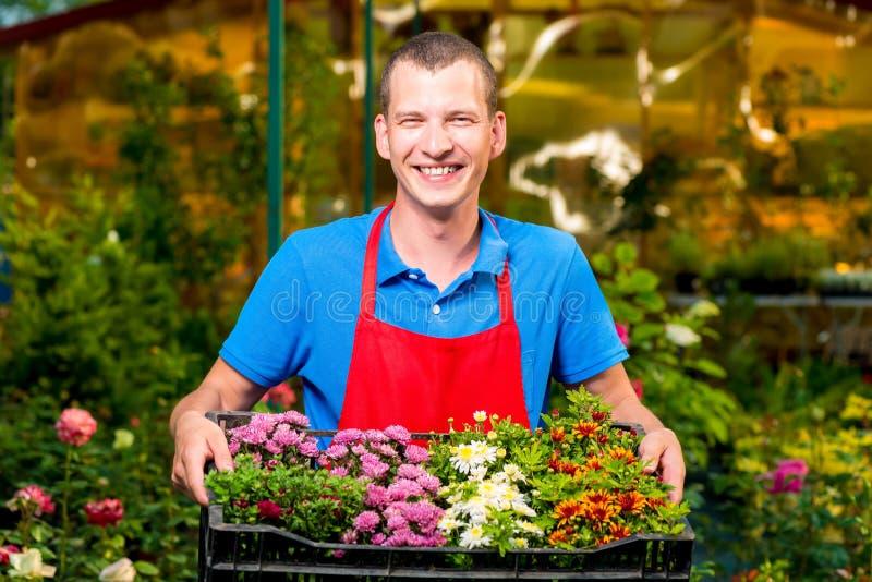 La femme d'affaires réussie se tenant dans sa jeune plante de mains fleurit photo stock