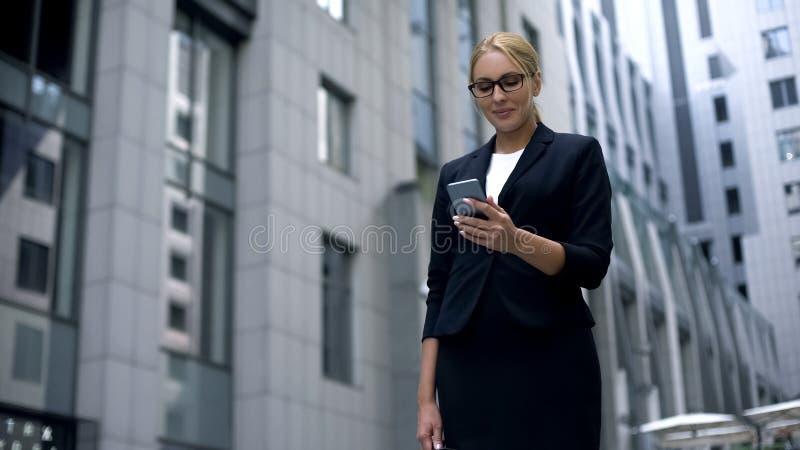 La femme d'affaires reçoit l'avis au téléphone portable au sujet de la location, promotion image stock