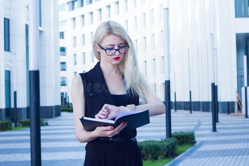 La femme d'affaires regarde l'horloge sur le fond du centre d'affaires image libre de droits