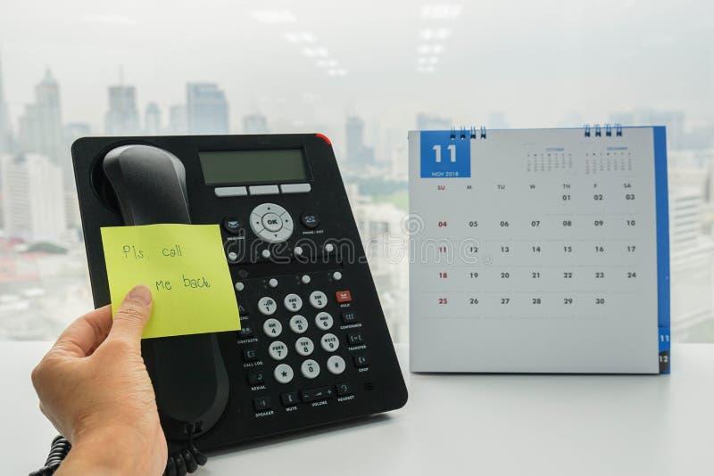la femme d'affaires a remis le post-it de l'appel j'au téléphone d'IP de collègue photo stock