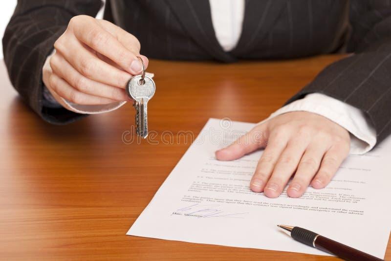 La femme d'affaires retient la clé et le contrat dans des mains photographie stock libre de droits