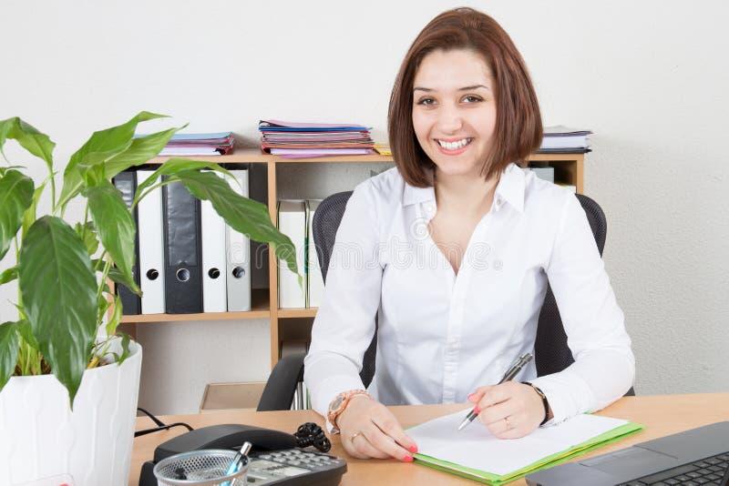 La femme d'affaires s'asseyant dans le bureau avec des doigts remet toucher son menton photo libre de droits
