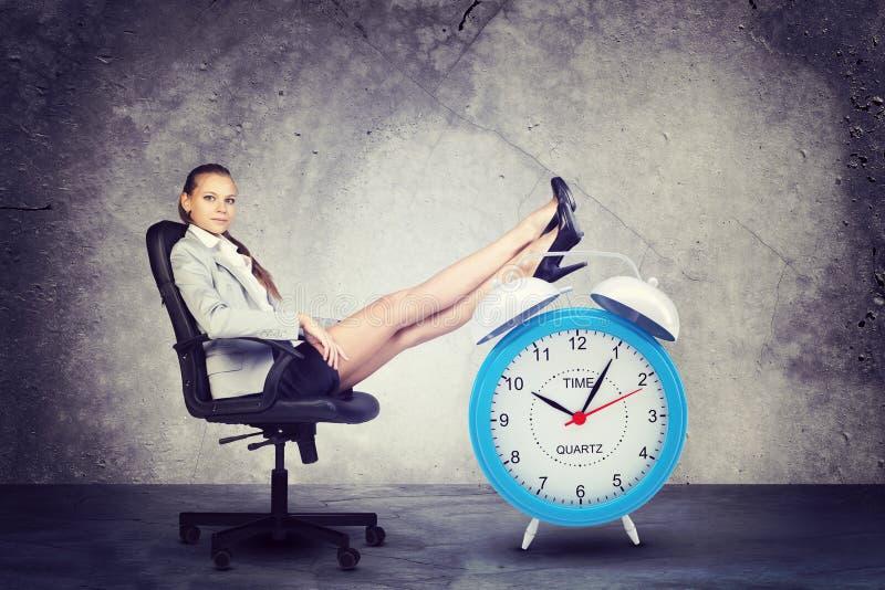 La femme d'affaires s'assied dans la chaise Mettez vos pieds dessus photographie stock libre de droits