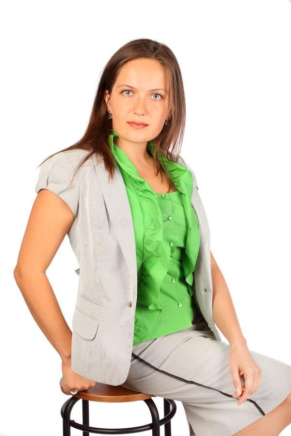 La femme d'affaires s'assied sur des selles dans le studio photographie stock libre de droits