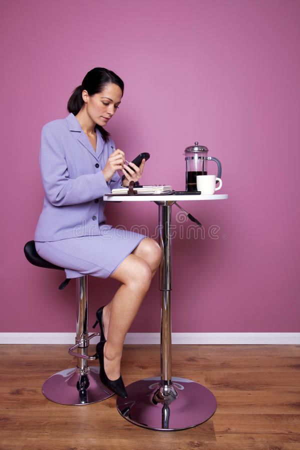 La femme d'affaires s'est assise dans un fonctionnement de café photographie stock libre de droits