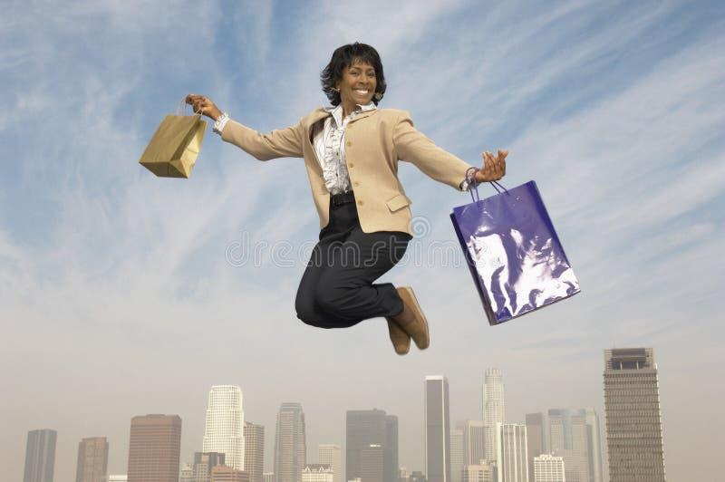 La femme d'affaires sautant avec des sacs à provisions photos stock