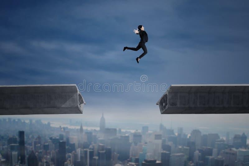 La femme d'affaires sautant par-dessus un espace dans le pont image libre de droits