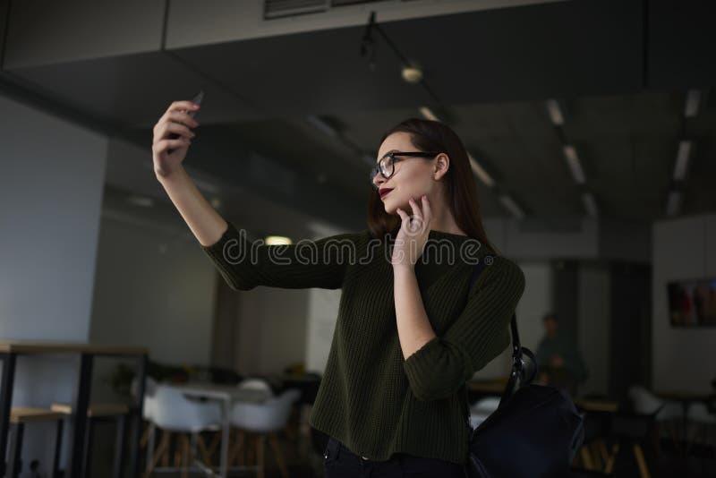 La femme d'affaires soulève ses qualifications dans une université privée à la mode utilisant la connexion internet 4G images libres de droits
