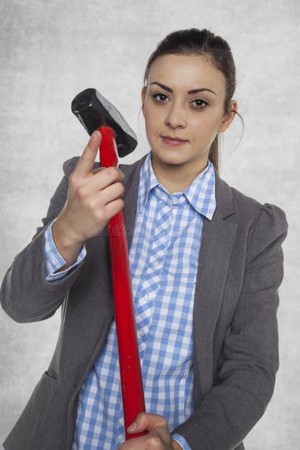 La femme d'affaires tient un grand marteau images libres de droits