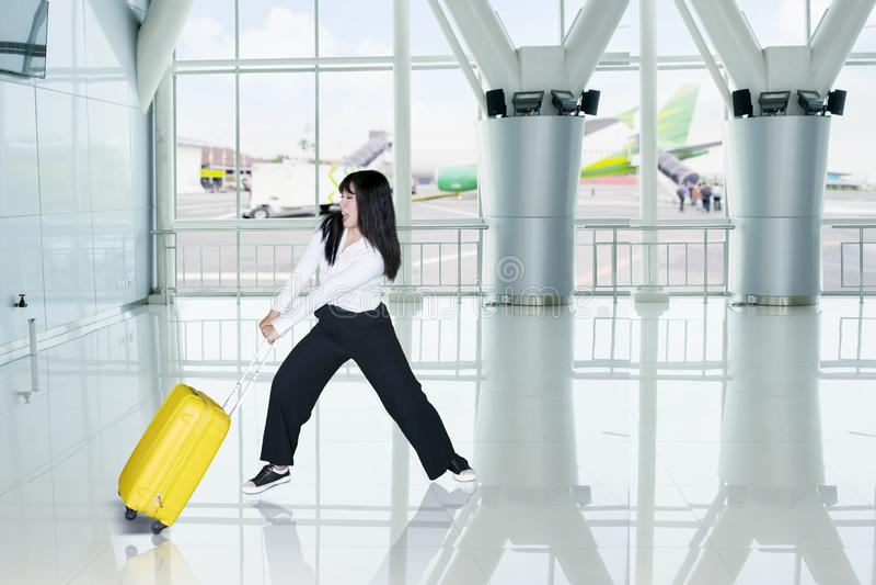 La femme d'affaires tire son bagage lourd dans l'aéroport photos libres de droits
