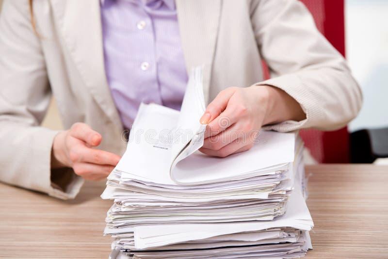 La femme d'affaires travaillant avec la pile de papiers photos libres de droits