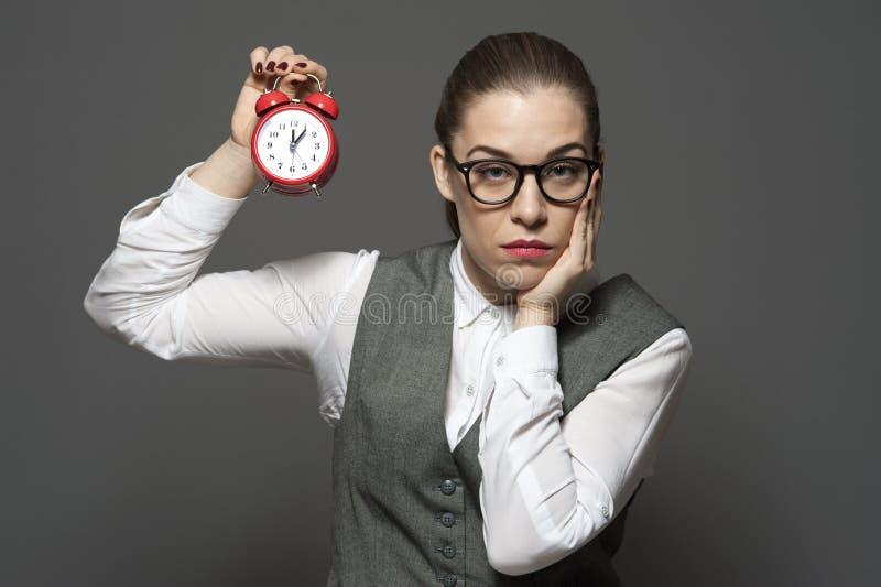La femme d'affaires triste est nerveuse tenant un réveil image libre de droits