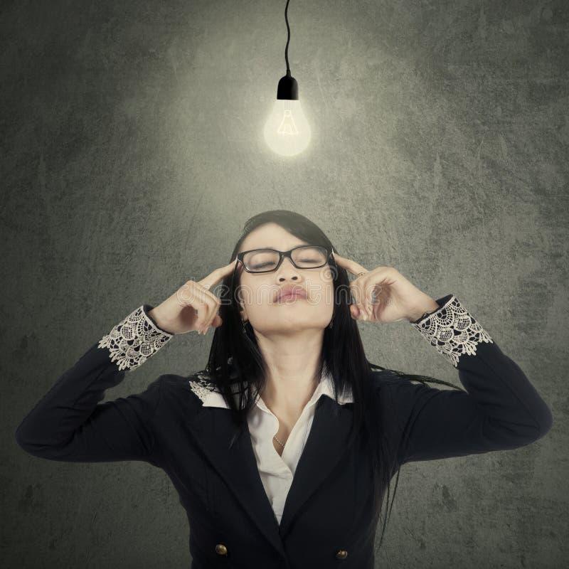 La femme d'affaires trouve la solution sous la lampe image stock