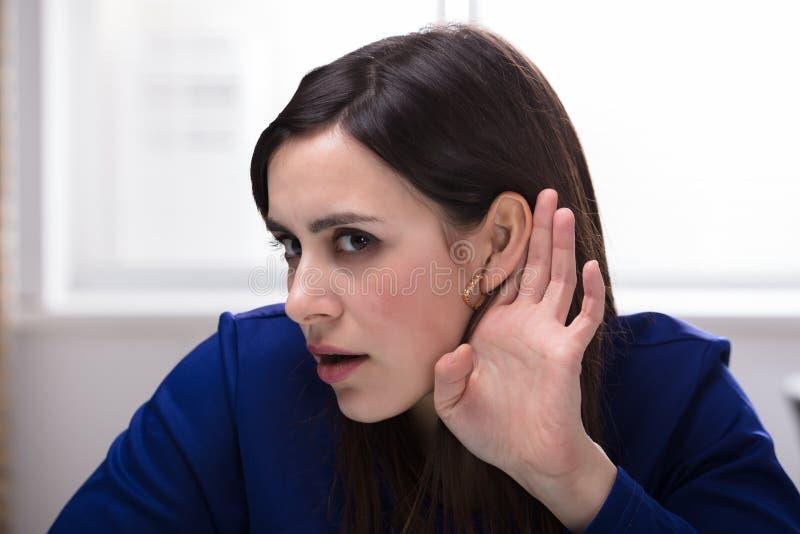 La femme d'affaires Trying To Hear avec remettent l'oreille image stock