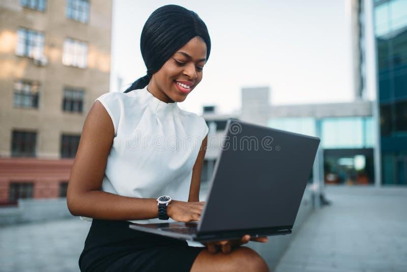 La femme d'affaires utilise l'ordinateur portable contre l'immeuble de bureaux photo libre de droits