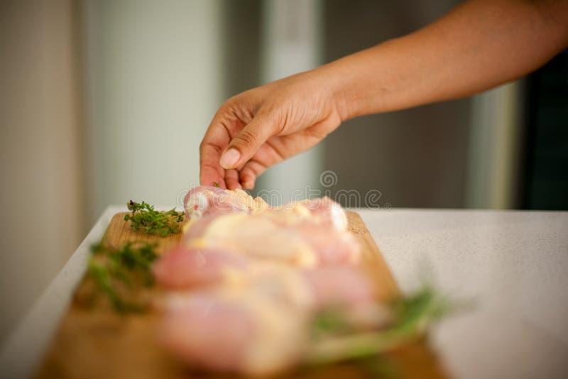 La femme d'afro-américain atteint pour un morceau de poulet, sa main photo stock