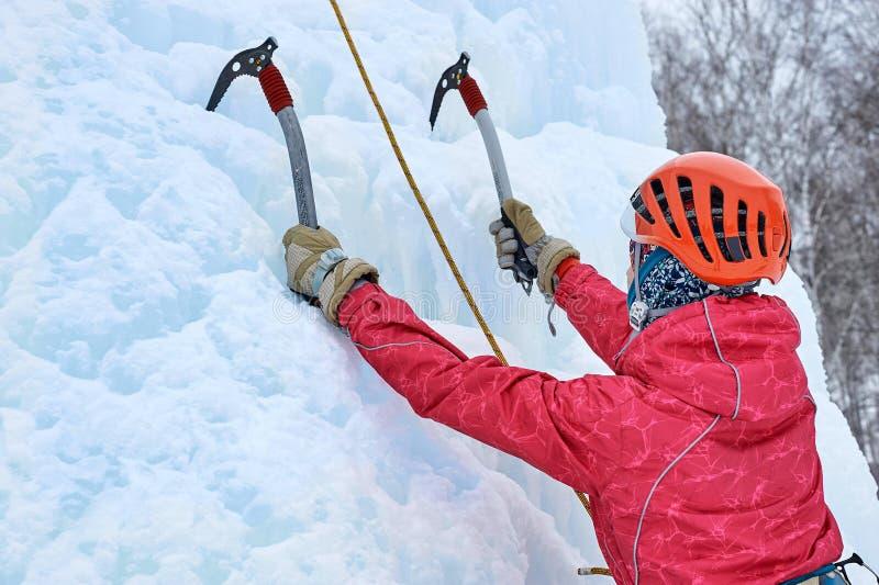 La femme d'alpiniste avec de la glace usine la hache dans le casque orange escaladant un grand mur de glace Portrait de sports en photographie stock libre de droits