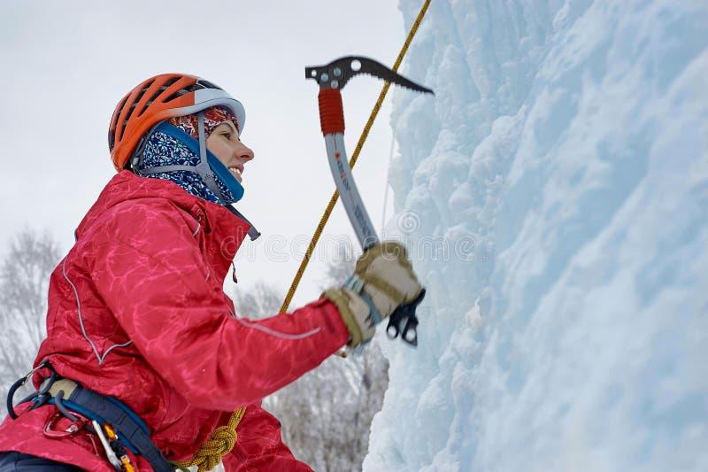 La femme d'alpiniste avec de la glace usine la hache dans le casque orange escaladant un grand mur de glace Portrait de sports en photographie stock