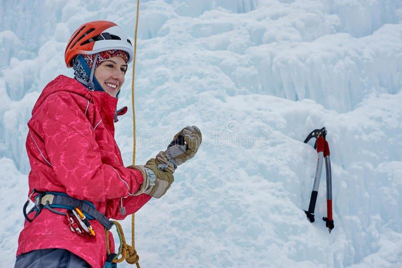 La femme d'alpiniste avec de la glace usine la hache dans le casque orange montant un l image stock