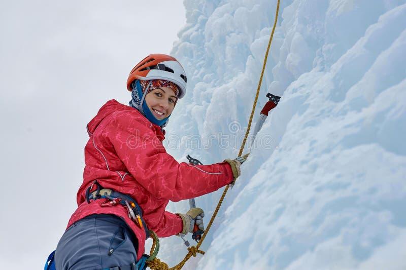 La femme d'alpiniste avec de la glace usine la hache dans le casque orange montant un l photographie stock