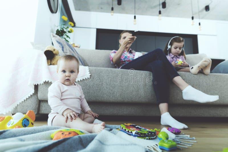 La femme d'AThe et la fille s'asseyent sur le divan et ne suivent pas le bébé Le bébé s'assied sur le plancher photographie stock libre de droits
