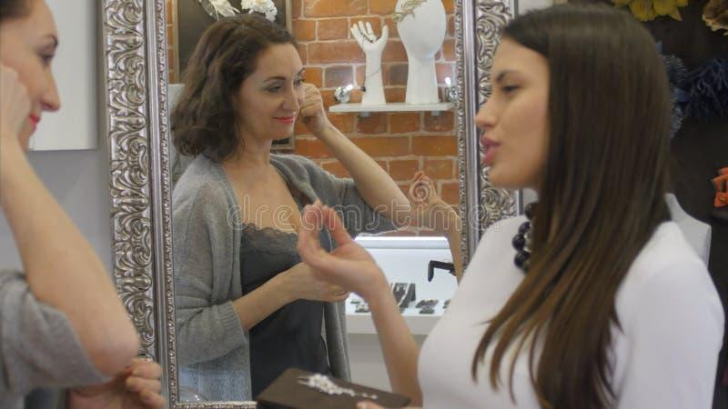La femme d'Eleant essaye une boucle d'oreille et regarde le miroir photos libres de droits
