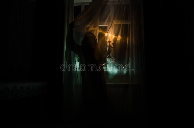 La femme d'horreur dans le concept effrayant de Halloween de scène de main de fenêtre de cage en bois de prise a brouillé la silh images stock