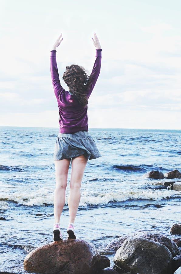 La femme d'une chevelure bouclée dans la robe et le pull molletonné sur la mer échouent photographie stock