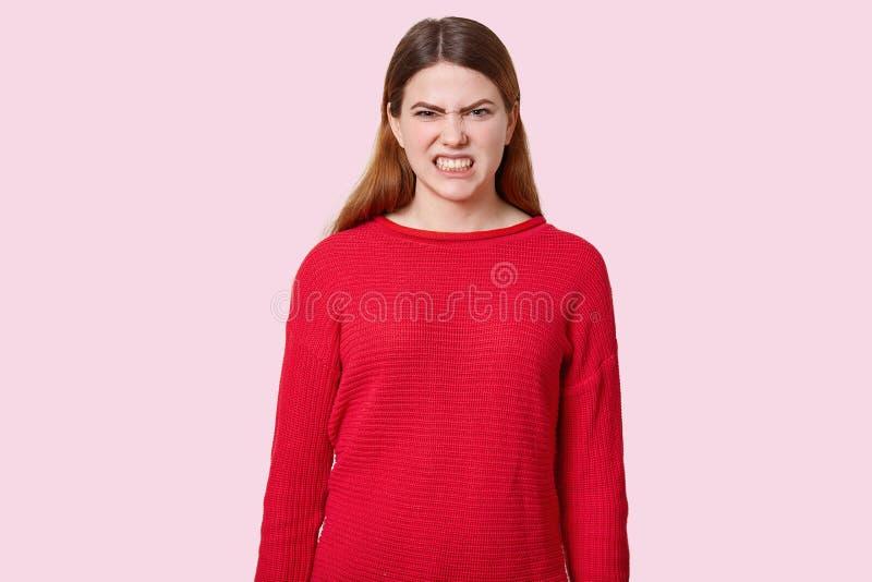 La femme d'une chevelure foncée mécontente serre des dents, fronce les sourcils visage avec le mécontentement, habillé dans le ch photo libre de droits