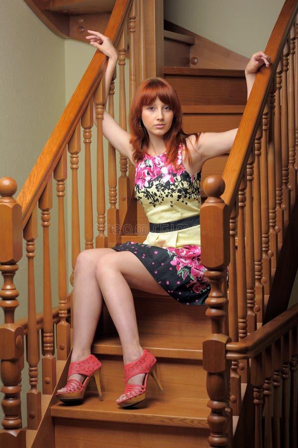 La femme d'une chevelure rouge s'asseyant dessus wodden des escaliers photographie stock
