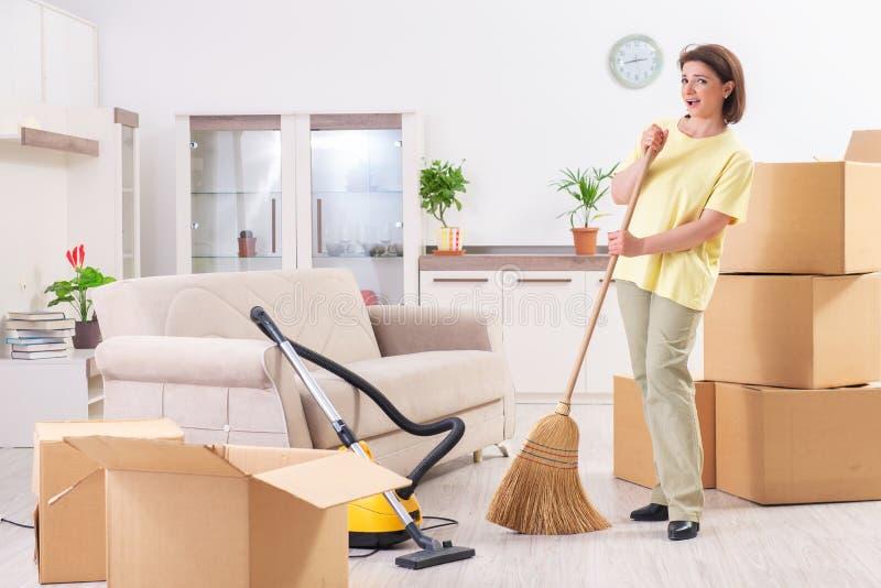 La femme d'une cinquantaine d'années nettoyant le nouvel appartement photos stock