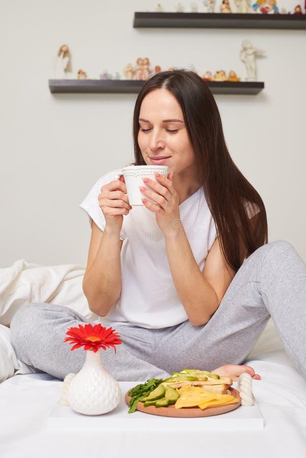 La femme dans des pyjamas apprécie le petit déjeuner sain images stock