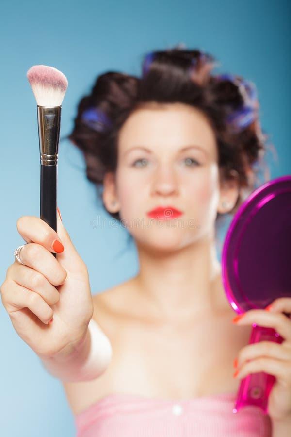 La femme dans des rouleaux de cheveux tient la brosse de maquillage photo stock