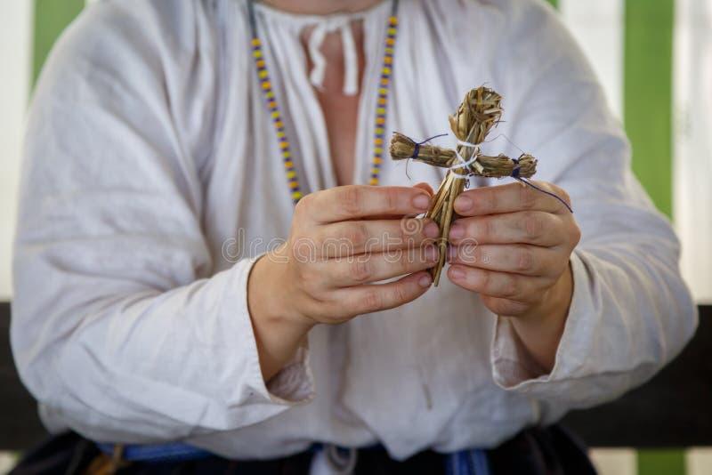 La femme dans des v?tements ethniques russes fait un petit jouet de la paille photographie stock libre de droits