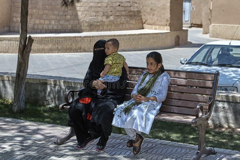 La femme dans des vêtements islamiques s'assied sur le banc avec deux enfants photos stock