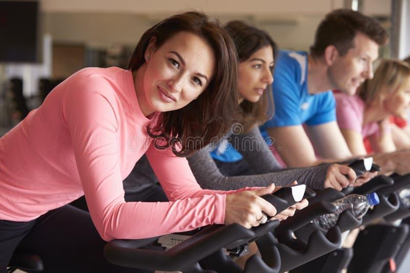 La femme dans la classe de rotation à un gymnase se tourne et sourit vers l'appareil-photo photos stock