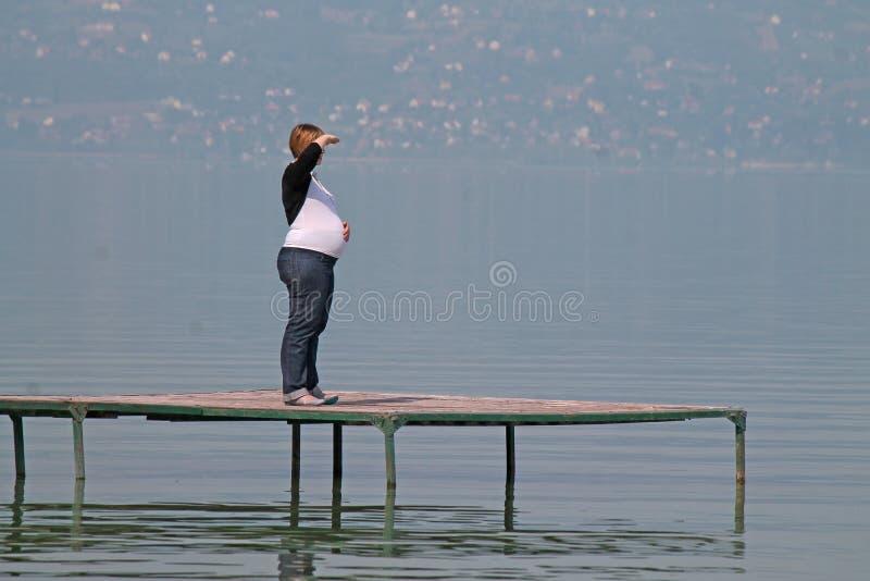 La femme dans la distance observe sur le pilier images libres de droits