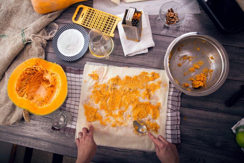 La femme dans la fabrication de cuisine prépare un tarte avec le potiron photo stock