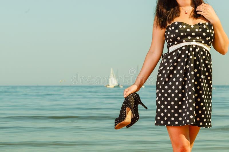 La femme dans la rétro robe tenant des chaussures s'approchent de la mer images stock
