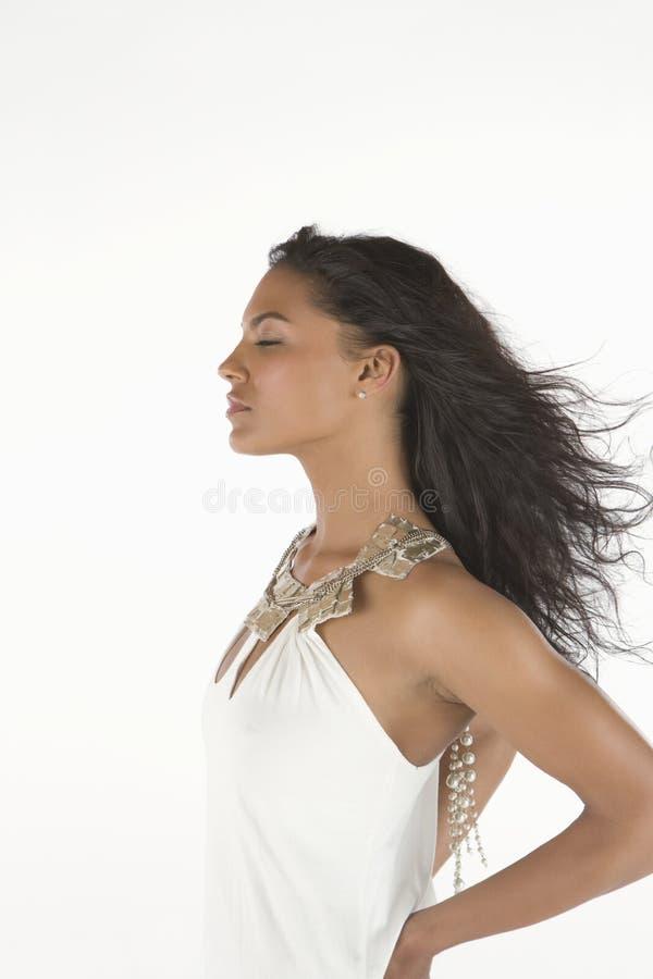 La femme dans la robe blanche se tient avec des yeux fermés image stock